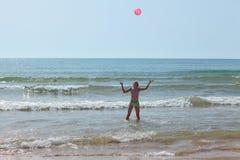 Muchacha con una bola roja en el mar entre las ondas Fotos de archivo