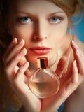 Muchacha con una botella de perfume en sus manos Imagen de archivo