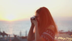 Muchacha con una cámara del vintage Playa, puesta del sol, viento almacen de metraje de vídeo
