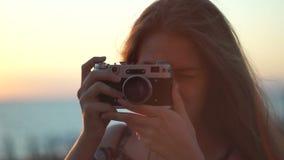 Muchacha con una cámara del vintage Playa, puesta del sol, viento almacen de video