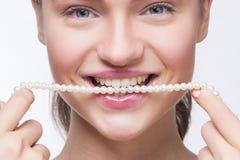 Muchacha con una cadena de perlas en su boca Imagen de archivo