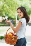 Muchacha con una cesta de fruta y verdura Foto de archivo
