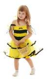 Muchacha con una cesta en traje de la abeja Foto de archivo