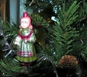 Muchacha con una cesta la Navidad del vintage juega en fondo del árbol del Año Nuevo Imágenes de archivo libres de regalías