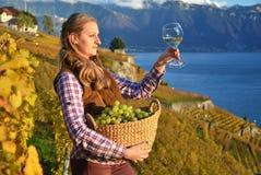 Muchacha con una cesta llena de uvas Fotos de archivo