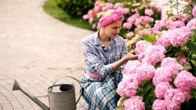Muchacha con una cinta rosada en sus cuidados principales para las flores La mujer con una regadera cultiva las flores en el jard