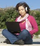 Muchacha con una computadora portátil y los auriculares Imágenes de archivo libres de regalías