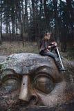 Muchacha con una espada en una cabeza de piedra foto de archivo libre de regalías