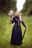 Muchacha con una espada que sostiene un búho Fotos de archivo