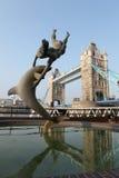 Muchacha con una estatua del delfín cerca del puente Reino Unido de la torre Fotos de archivo