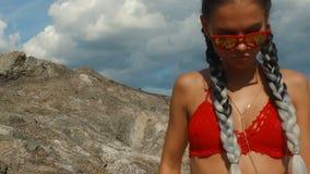 Muchacha con una figura perfecta en un traje de baño rojo en la playa almacen de metraje de vídeo