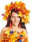 Muchacha con una guirnalda de las hojas de otoño en la pista. Imagen de archivo libre de regalías