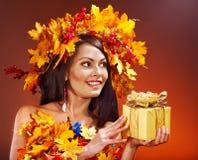 Muchacha con una guirnalda de las hojas de otoño en la pista. Foto de archivo libre de regalías