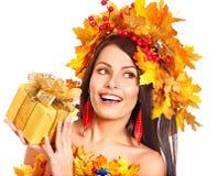 Muchacha con una guirnalda de las hojas de otoño en la cabeza. Foto de archivo