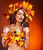 Muchacha con una guirnalda de las hojas de otoño en la pista. Fotos de archivo