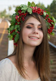 Muchacha con una guirnalda en su viburnum principal Fotos de archivo