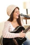 Muchacha con una guitarra que canta en el micrófono Fotos de archivo libres de regalías