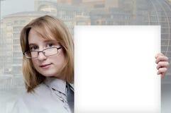 Muchacha con una hoja de papel limpia Fotos de archivo