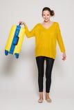 Muchacha con una maleta amarilla Fotografía de archivo