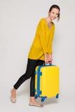 Muchacha con una maleta amarilla Fotos de archivo libres de regalías