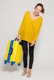 Muchacha con una maleta amarilla Fotografía de archivo libre de regalías