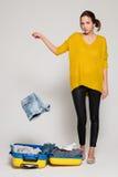 Muchacha con una maleta amarilla Imagen de archivo