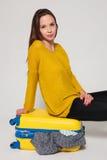 Muchacha con una maleta amarilla Imagenes de archivo