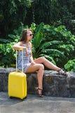 Muchacha con una maleta amarilla en un centro turístico Foto de archivo
