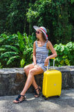Muchacha con una maleta amarilla en un centro turístico Fotos de archivo libres de regalías
