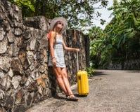 Muchacha con una maleta amarilla en un centro turístico Fotos de archivo
