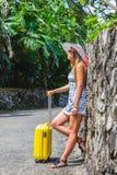 Muchacha con una maleta amarilla en un centro turístico Imágenes de archivo libres de regalías