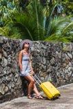 Muchacha con una maleta amarilla en un centro turístico Fotografía de archivo