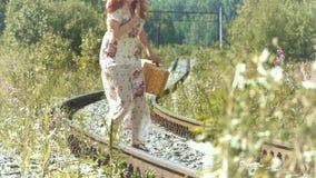 Muchacha con una maleta en las pistas ferroviarias almacen de metraje de vídeo