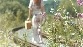 Muchacha con una maleta en las pistas ferroviarias metrajes
