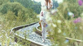 Muchacha con una maleta en las pistas ferroviarias almacen de video