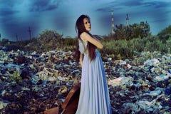 Muchacha con una maleta que se coloca en una descarga de basura sobre fondo del cielo azul Foto de archivo libre de regalías