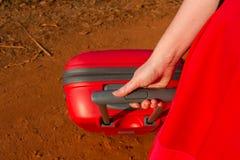 Muchacha con una maleta roja Fotografía de archivo