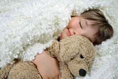 Muchacha con una manta blanca y un perro de juguete suave Fotografía de archivo libre de regalías