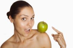 Muchacha con una manzana verde en su hombro imagenes de archivo