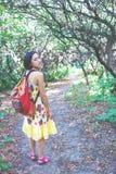 Muchacha con una mochila que camina a través del bosque Fotos de archivo