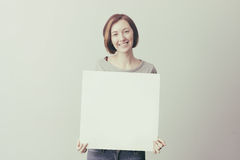 Muchacha con una muestra de publicidad blanca Imagen de archivo