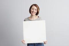 Muchacha con una muestra de publicidad blanca Imágenes de archivo libres de regalías