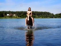 Muchacha con una natación del caballo en el lago Imágenes de archivo libres de regalías