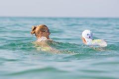 Muchacha con una natación del niño en el mar Fotos de archivo