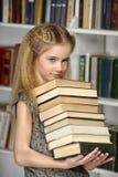 Muchacha con una pila de libros Fotografía de archivo libre de regalías