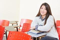 Muchacha con una pila de libros en su sala de clase Fotografía de archivo libre de regalías
