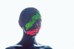 Muchacha con una pintura negra en la cara Verde y rojo Fotografía de archivo
