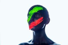 Muchacha con una pintura negra en la cara Verde y rojo Imágenes de archivo libres de regalías