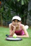 Muchacha con una raqueta de tenis y una pelota de tenis Fotos de archivo libres de regalías