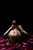 Muchacha con una rosa en un fondo negro Foto de archivo libre de regalías
